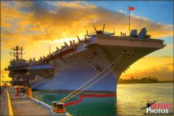 A dramatic sunset behind the USS AbrahamLincoln (CVN-72) Aircraft Carrier docked at Pearl Harbor Naval Station in Oahu, Hawaii.  HDR Image composed of three different photos - Photo by Britt Dietz