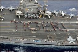 Tiger Cruise 2011 participants line up to spell TIGER! on the flight deck of the USS Abraham Lincoln (CVN-72) Aircraft Carrier in this photo taken from a Kighthawk Helicopter - Photo by the US NAVY