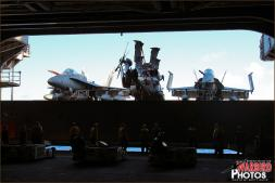 Two F/A-18C Hornets and one MH-60S Knighthawk are lowered on the starboard elevator of the USS Abraham Lincoln - Photo by Britt Dietz