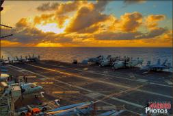 The sun sets with dramatic colors and rays of light over the flight deck of the USS Abraham Lincoln (CVN-72) as seen from Vultures Row - Photo by Britt Dietz
