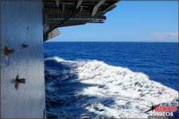 The large waves generated by the USS Abraham Lincoln Aircraft Carrier come head to head with slight swells out to sea just beyond Oahu, Hawaii - Photo by Britt Dietz