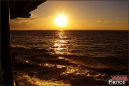 The sun rises very vividly over the Pacific Ocean taken from the starboard side of the USS Abraham Lincoln (CVN-72) US Navy Aircraft Carrier. - Photo by Britt Dietz