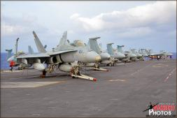 Boeing F/A-18C Hornets and Boeing F/A-18F Super Hornets from various squadrons aboard the USS Abraham Lincoln Aircraft Carrier sit lined up on the forward catapults being prepped for launch in a few days. - Photo by Britt Dietz