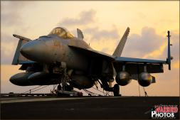A Boeing F/A-18E Super Hornet sits silently on the windy aft flight deck of the USS Abraham Lincoln Aircraft Carrier (CVN-72) during a beautiful pacific ocean sunset. - Photo by Britt Dietz